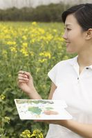 Woman painting at the rape field