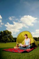 Woman reading book while camping in the park