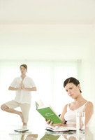 Woman reading book while her boyfriend is meditating in the background