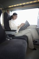 Woman reading newspaper while traveling on the train