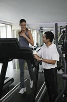 Woman running on treadmill, personal trainer watching