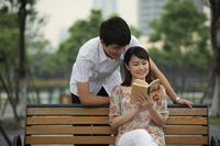 Woman sitting on bench reading book, man watching from behind
