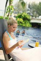 Woman sitting on lounge chair by the pool reading a book