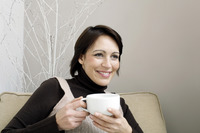 Woman sitting on the couch holding a cup of coffee