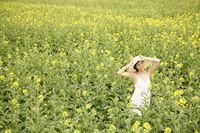 Woman standing at the rape field, smiling