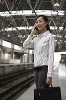 Woman standing on train station platform talking on the phone