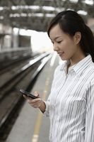 Woman standing on train station platform text messaging on the phone