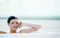 Woman talking on the mobile phone while sitting in the bathtub