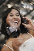 Woman talking on the phone and holding a glass of red wine
