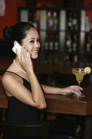 Woman talking on the phone at the bar
