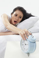 Woman turning off alarm clock