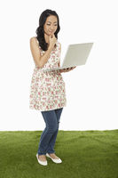 Woman using a laptop while standing, contemplating