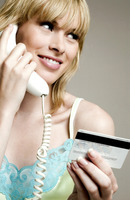 Woman using credit card over the telephone