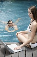 Woman using laptop by the pool side, man swimming towards woman