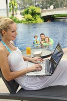 Woman using laptop on lounge chair