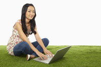 Woman using laptop while sitting