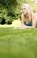 Woman with a book on the grass looking at the camera