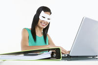 Woman with a cat mask using laptop