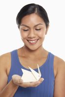 Woman with a miniature paper rabbit on her palm