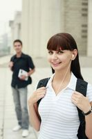 Woman with backpack listening to music on portable mp3 player