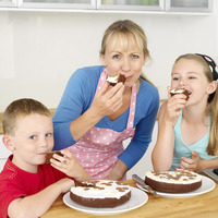 Woman with boy and girl enjoying cakes in the kitchen