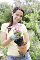 Woman with gardening gloves holding a pot flower