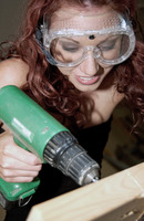 Woman with goggles drilling a wood
