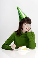 Woman with party hat eating cake