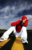 Woman with red hooded jacket sitting in the middle of the road