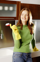 Woman with rubber gloves holding a brush