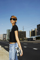 Woman with sunglasses holding a skateboard