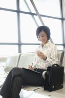 Woman writing on organizer while text messaging on the phone
