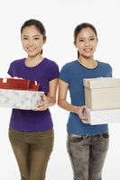 Women carrying a stack of gift boxes