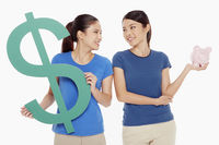 Women holding up a dollar sign and a piggy bank