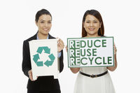 Women holding up a recycle bin and a placard
