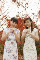 Women in cheongsam greeting with their hands clasped together