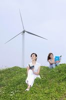 Women reading outdoors with wind mill in the background