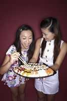 Young woman holding a tray of sushi, another young woman taking sushi with chopsticks