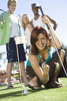 Young woman playing mini golf with friends