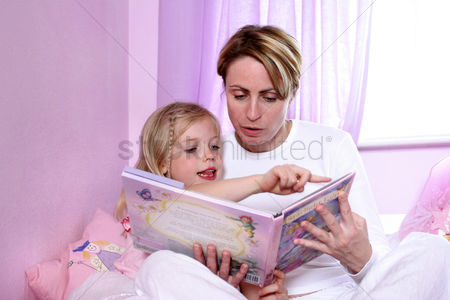 Girl : A woman sitting on the bed reading bedtime story for her daughter