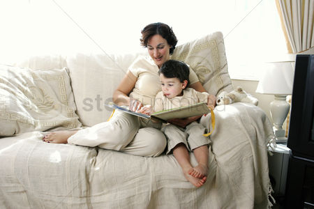 Cute : A woman sitting on the couch reading a story book for her young son