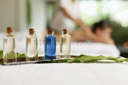 Spa : Bottles of massage oil  woman receiving back massage in the background