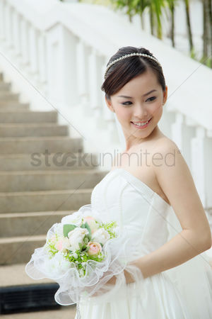 Wedding : Bride with a bouquet standing on stairway