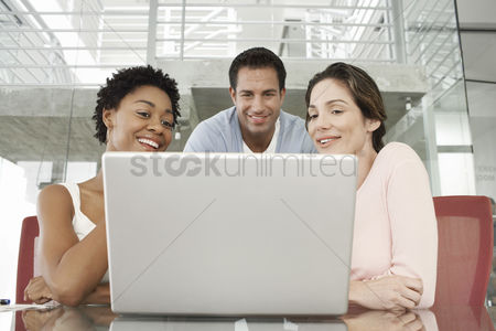 Interior : Business colleagues using laptop in office