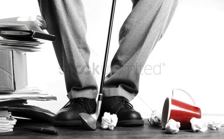 Business : Businessman hitting crumpled papers with golf club