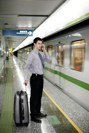 Interior : Businessman talking on the hand phone while waiting for the train