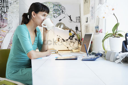 Food : Businesswoman mid-30s drinking by office desk