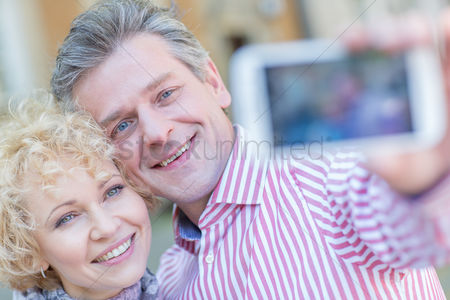 Selfie : Close-up of happy middle-aged couple taking selfie through smart phone