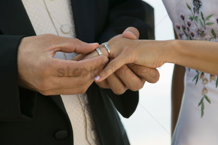Wedding : Groom placing ring on brides finger  close-up