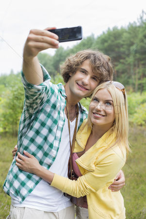Selfie : Happy young couple taking self portrait through cell phone in field